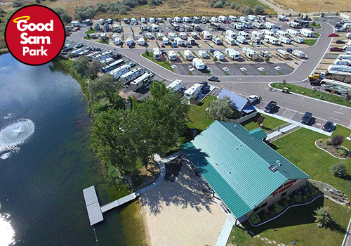 An aerial shot of an RV park with a green-roofed outbuilding and a t-shaped dock leading into a lake.