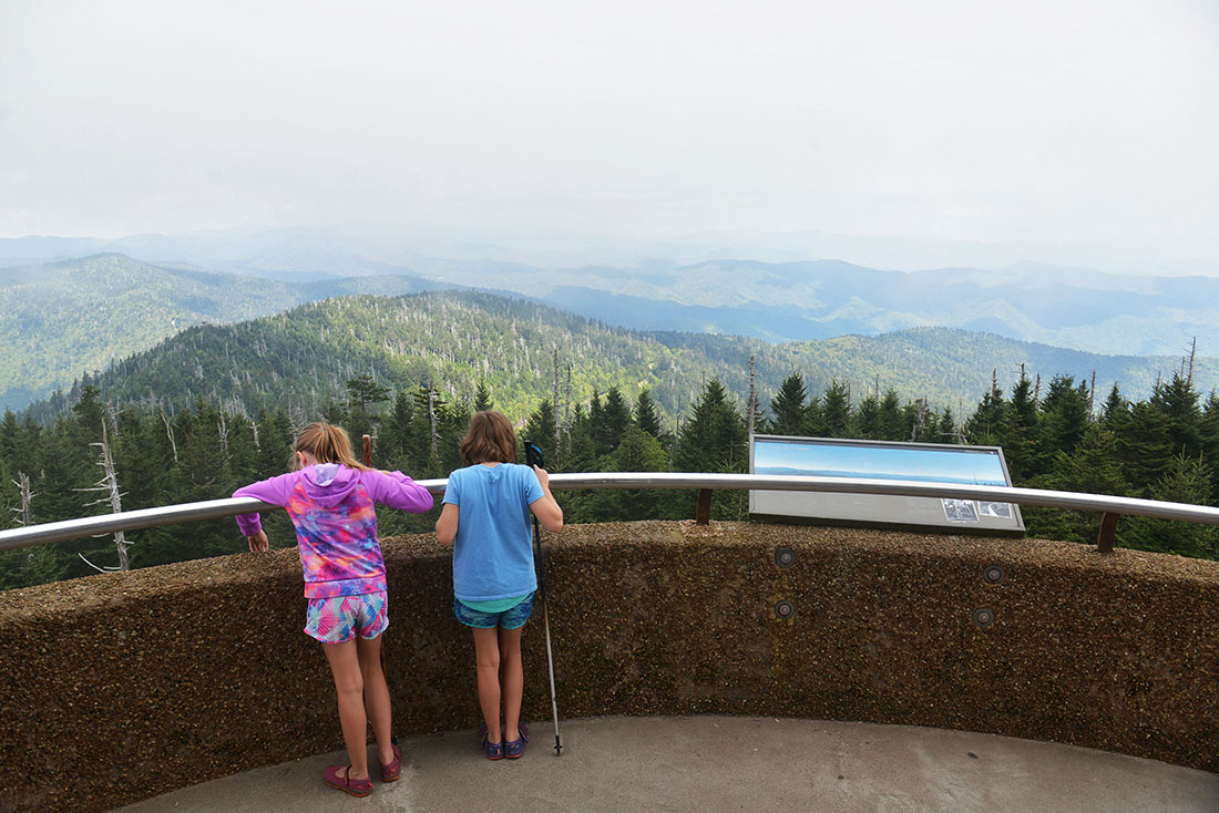 Two girls stand at a railing looking down over a mountainous landscape carpeted in forest.