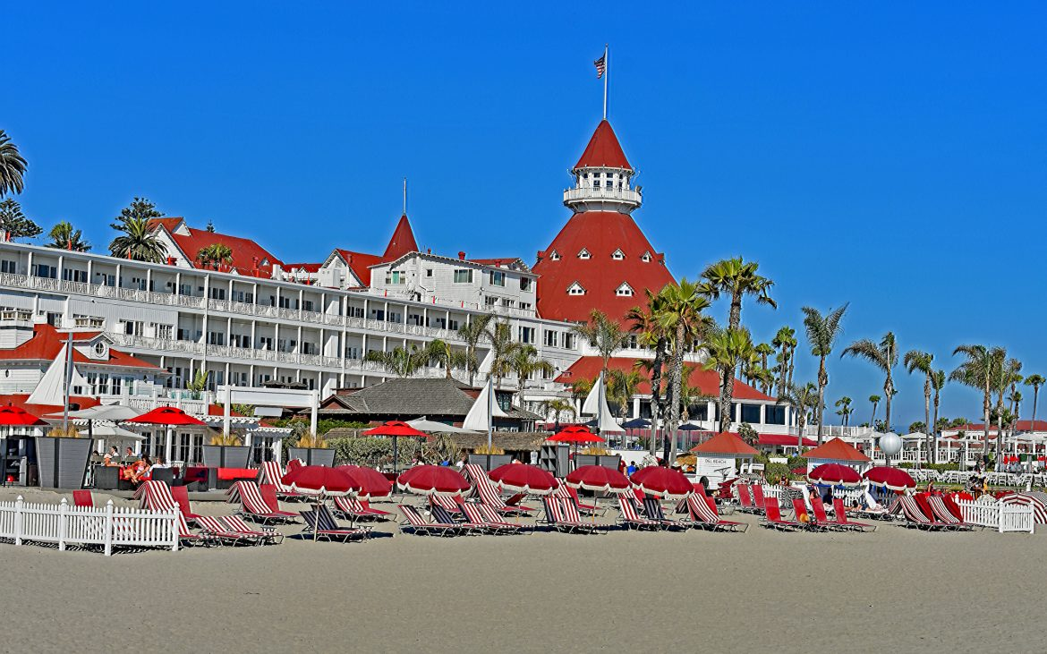 Red roofs hotel on beach with red and white striped lounge chairs