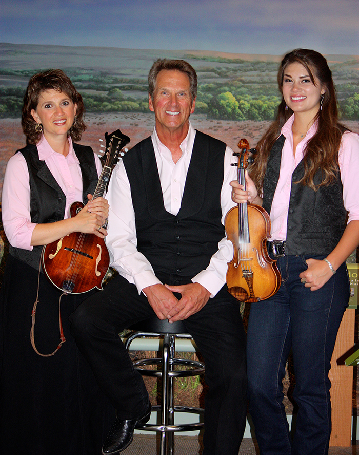 A musician in his 50s or 60s is flanked by two younger famale musicians, holding a mandolin and fiddle, respectively.