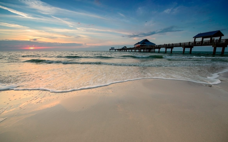 Sunset over beach shore next to pier