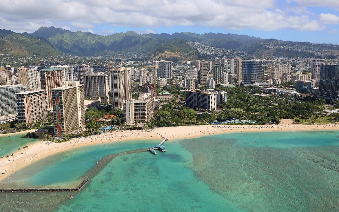 Ariel view of turquoise ocean and tall buildings in Hawaii