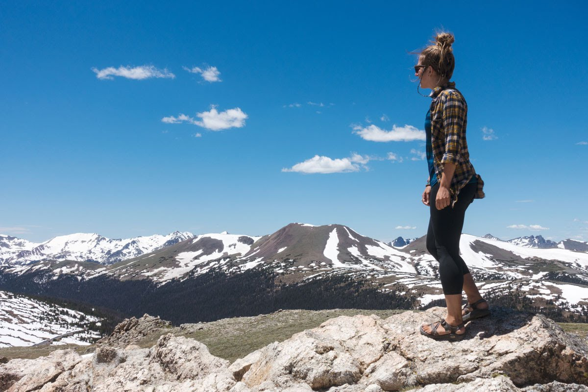 A woman walks along a rock outcropping with snow-capped peaks in the background.