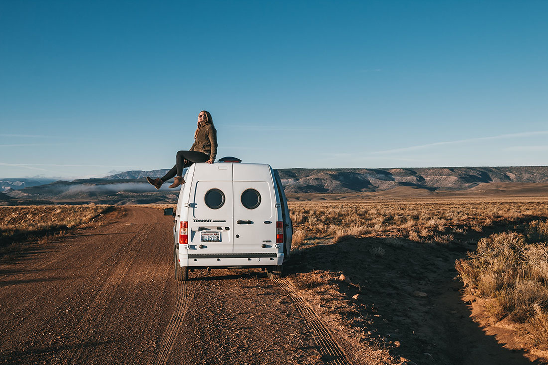 A woman wearing jacket and black pants on the roof of a camper van during sunset.
