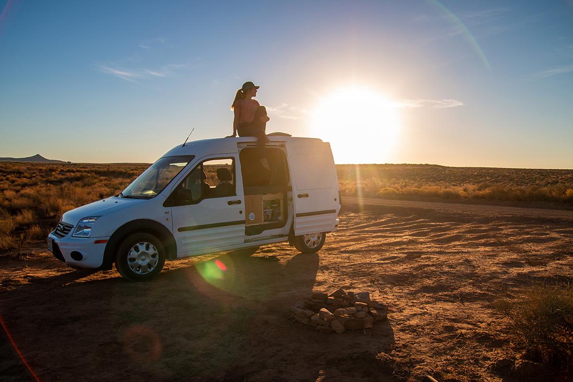 A woman sitting atop a white camper van as the sun sets on a desert horizon.