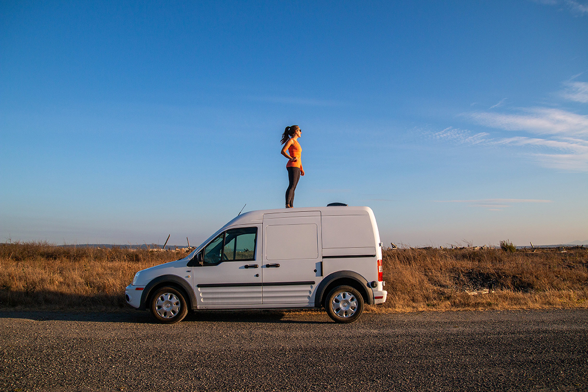A solitary travelers stands on top of a camper van facing the sunset.