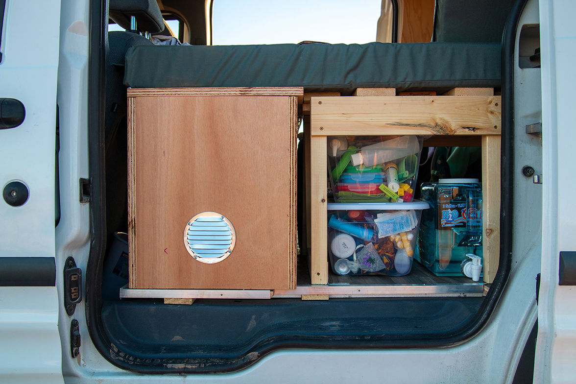 Storage containers — some in clear plastic boxes — inside of a camper van.