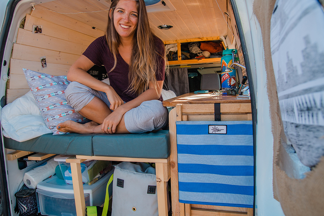 A solo traveler sitting in the back of her camper van.