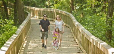 A family of three walks down a footbridge; the kid rides a bike.