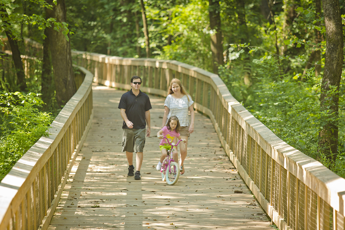 A family of three walks down a footbridge; the kid rides a bike.