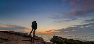 A man stands on rock outdropping facing the sun rising over the sea in Maine