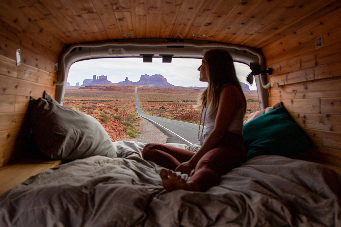 A young woman sitting in the rear of her camper van looks out at the stark mesas that line the desert horizon.