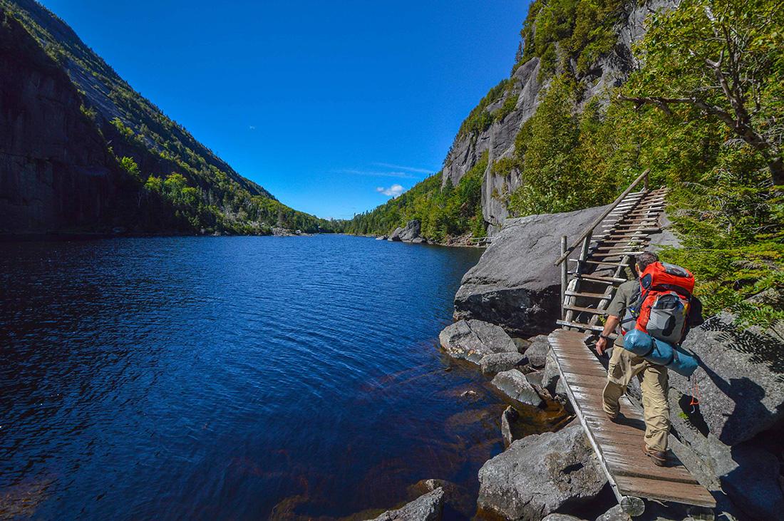 A man traverses a catwalk over rocks along the edge of a blue lake