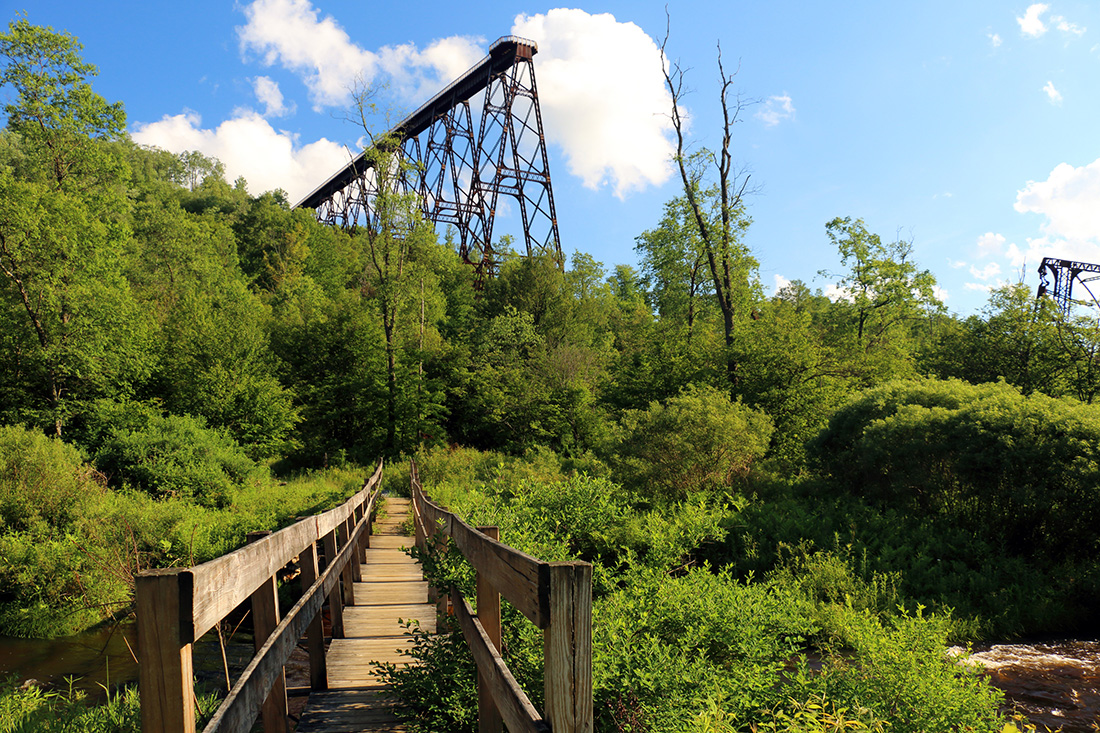 A wooden trail leads to a tall wooden observation platform on tall supports.