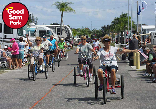 About 10 seniors riding tricycles roll down the main avenue of an RV park.