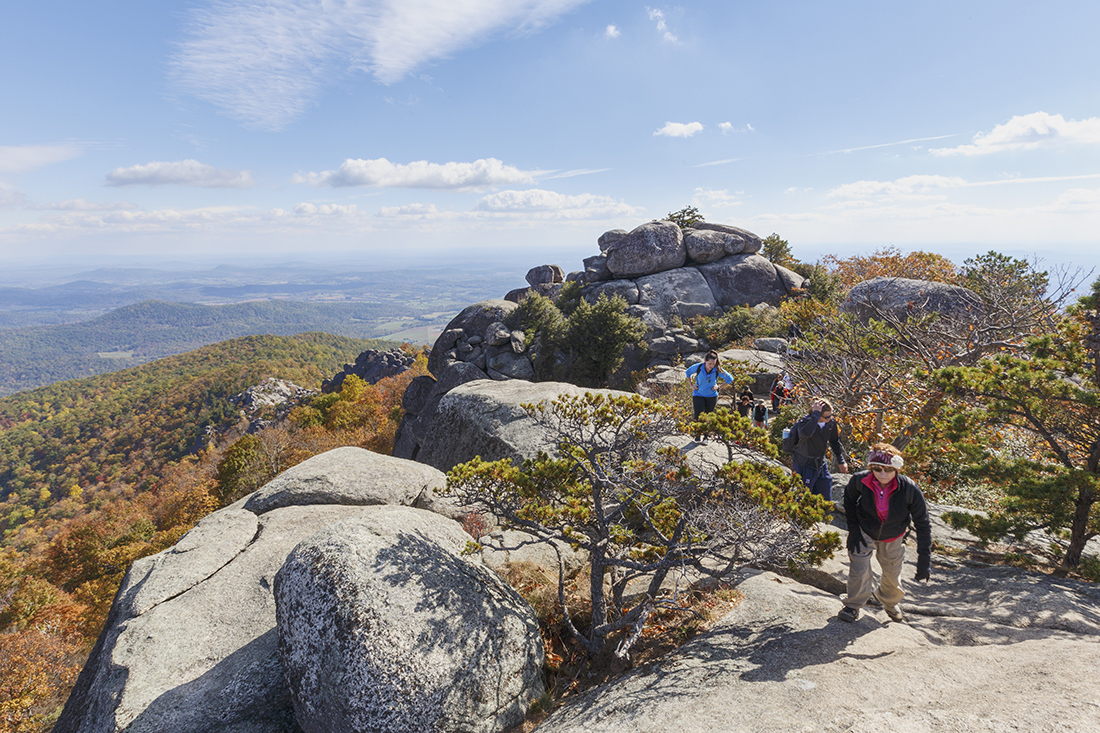 Hikers clamber up a steep rocky slope close to a summit with clear skies in the background.