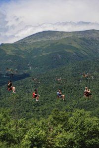A group fo zipline riders careen over a green valley with mountains in the background.