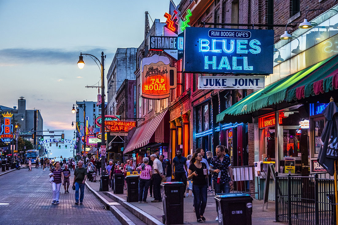 Main street of Memphis, Tennessee, at dusk showing Blues Hall and pub lit signs