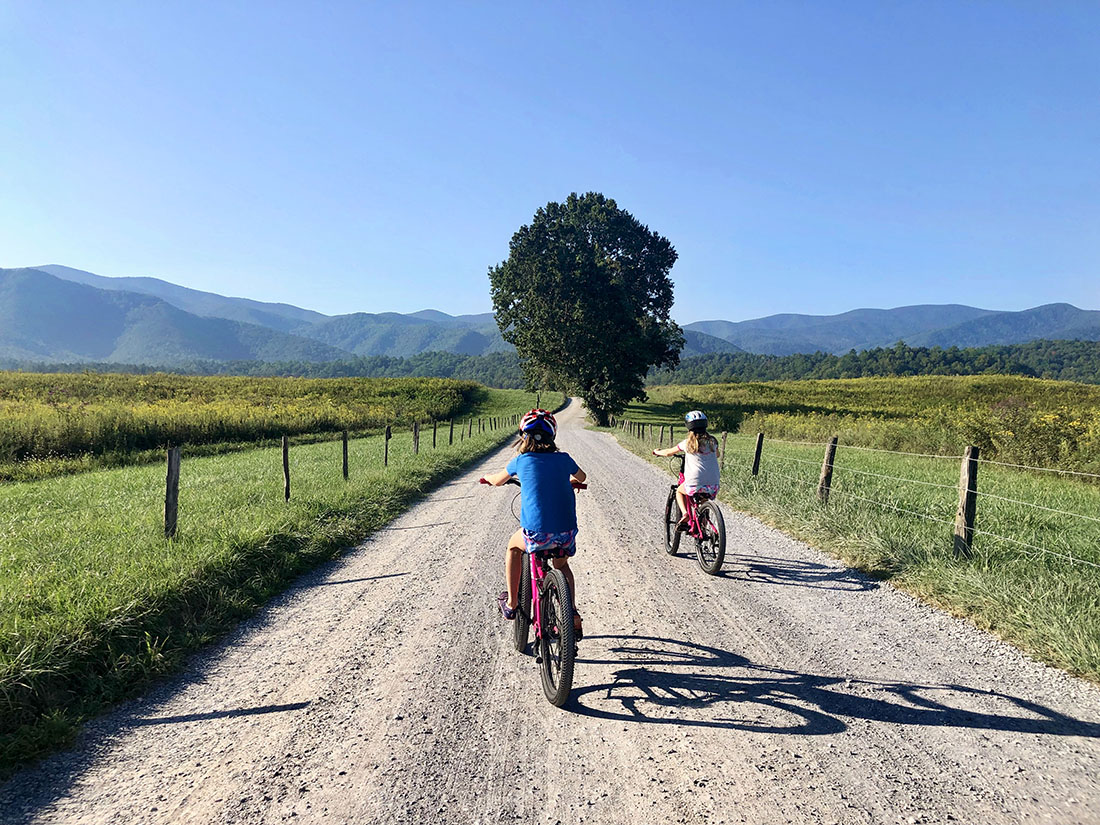 A pair of girls ride a dirt bike path toward mountains in the horizon.