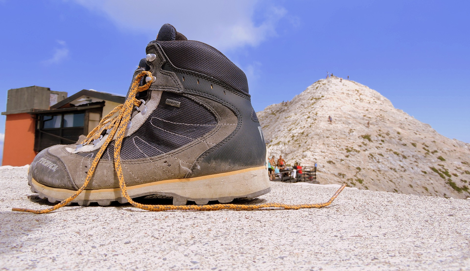 A lone hiking boot sits on a rock, laces askew.