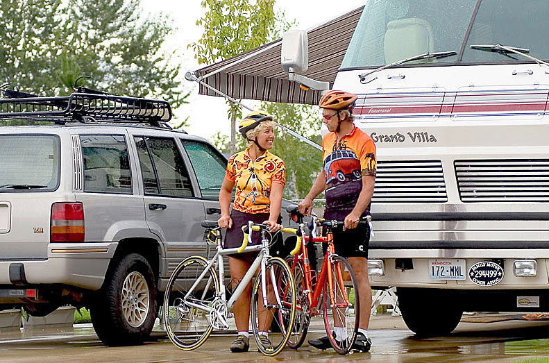A woman and man cyclist chat as they stand next to their bikes in front of an RV.