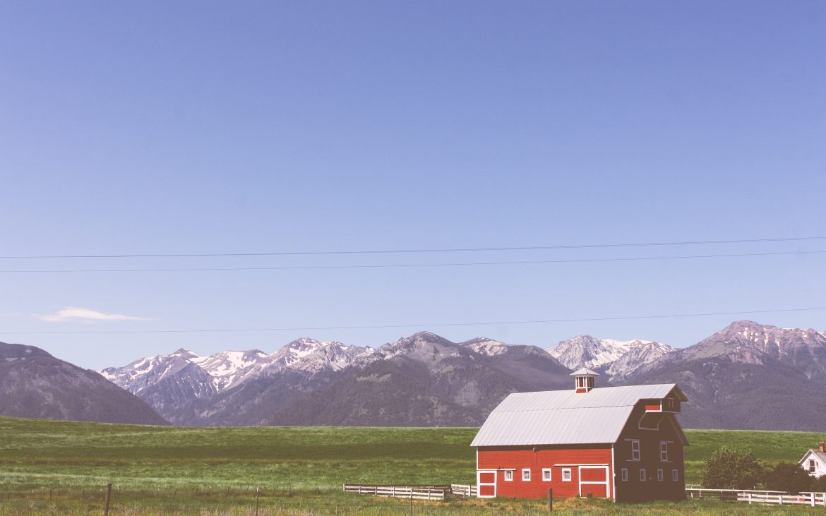 Scenic red barn in grassy valley, with snow-capped mountains in background