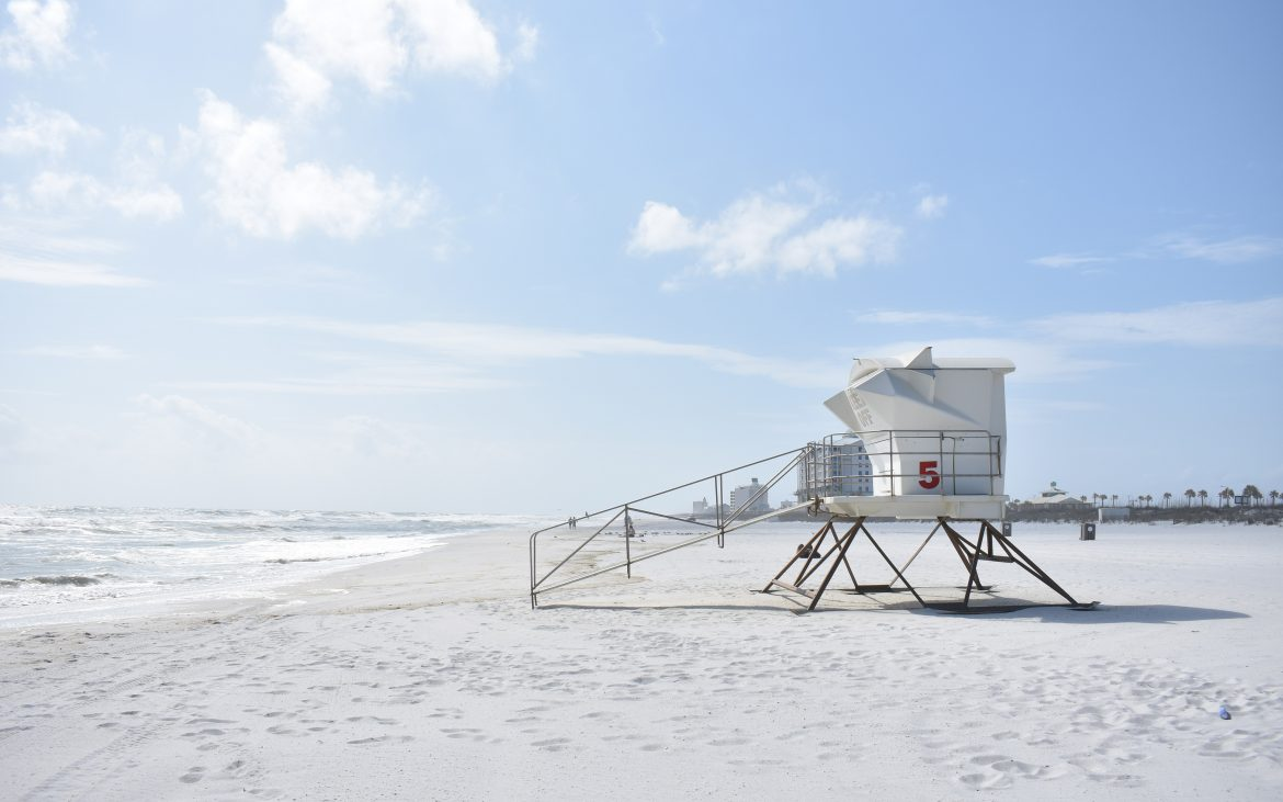 Side view of lifeguard tower on white sandy beach on sunny day