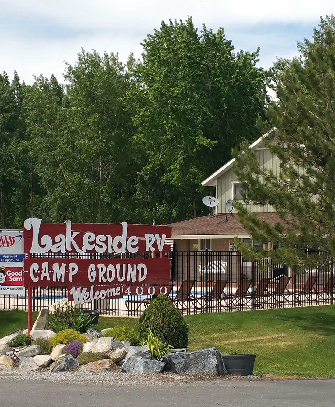 Lakeside RV Campground sign with building and pool in background.