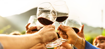 Hands holding long-stemmed glasses of red wine in a clinking, toasting motion.