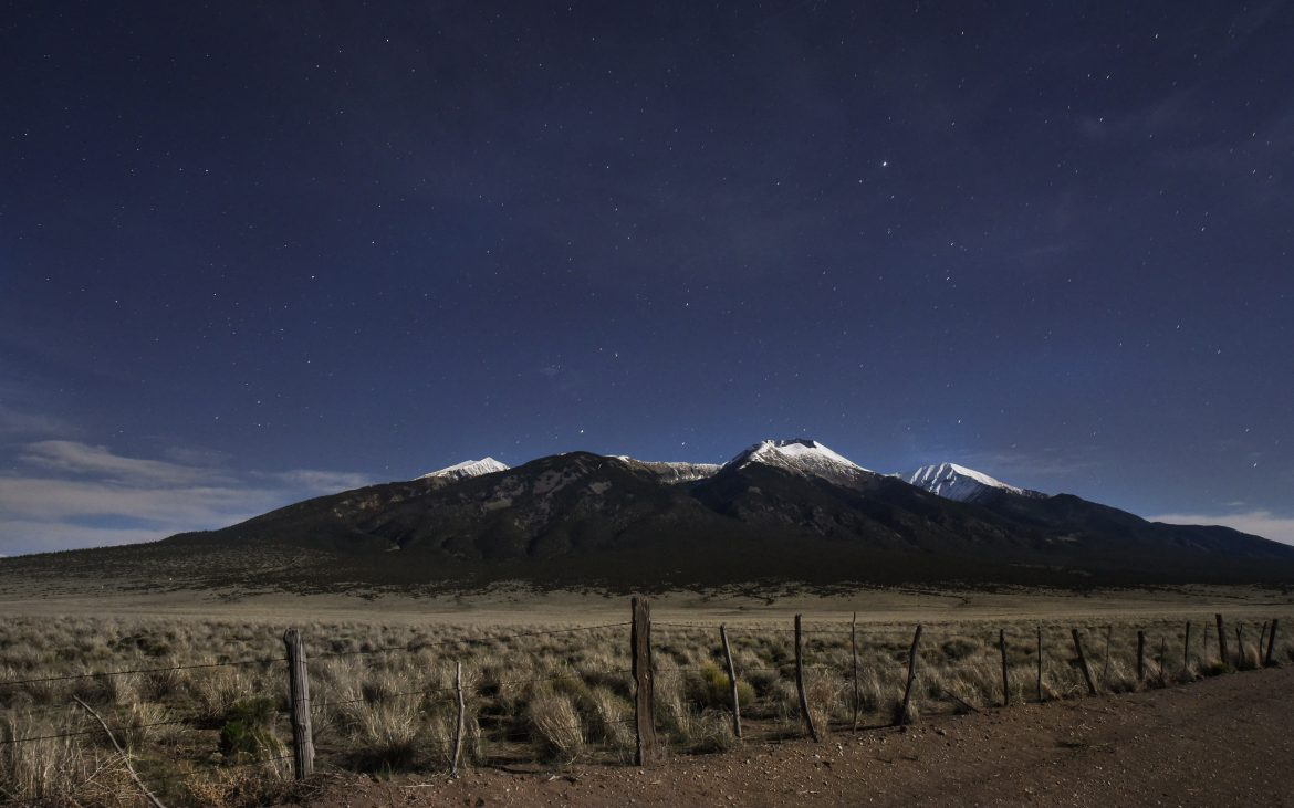 Snow capped mountains behind sand dunes and dirt road on starry night