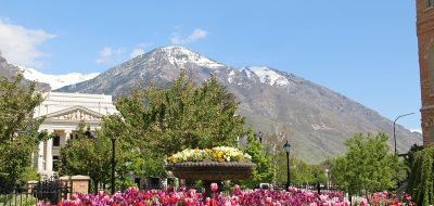 A view of a majestic mountain with flowers and greek revival building in the foregournd at lakeside rv campground