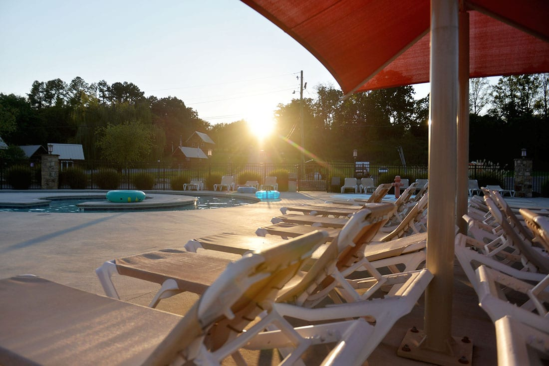 The sunsets over the horizon, shining its last rays on a row of chaise lounges sitting poolside.
