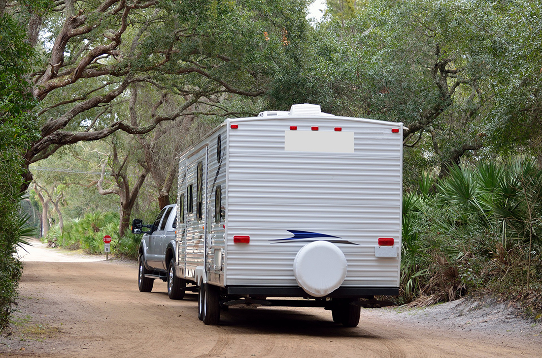 A travel trailer driving away from a camera down a dirt road.
