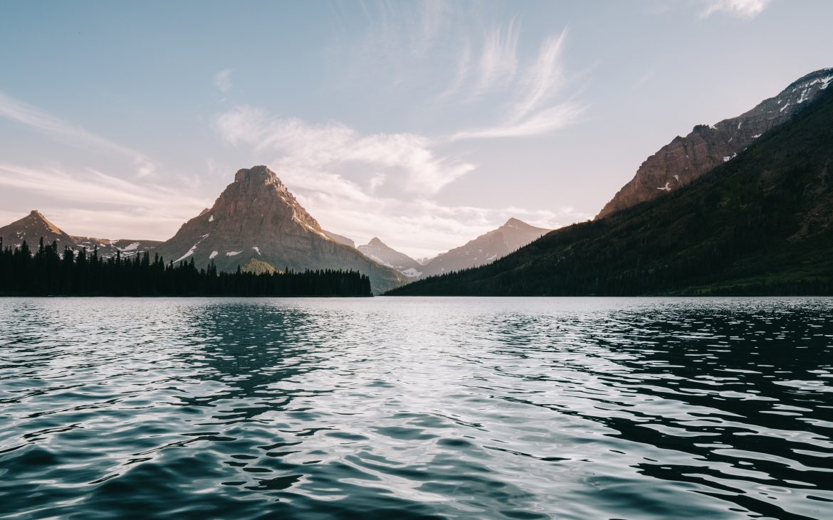 Glacier National Park lake with mountains in background on sunny day