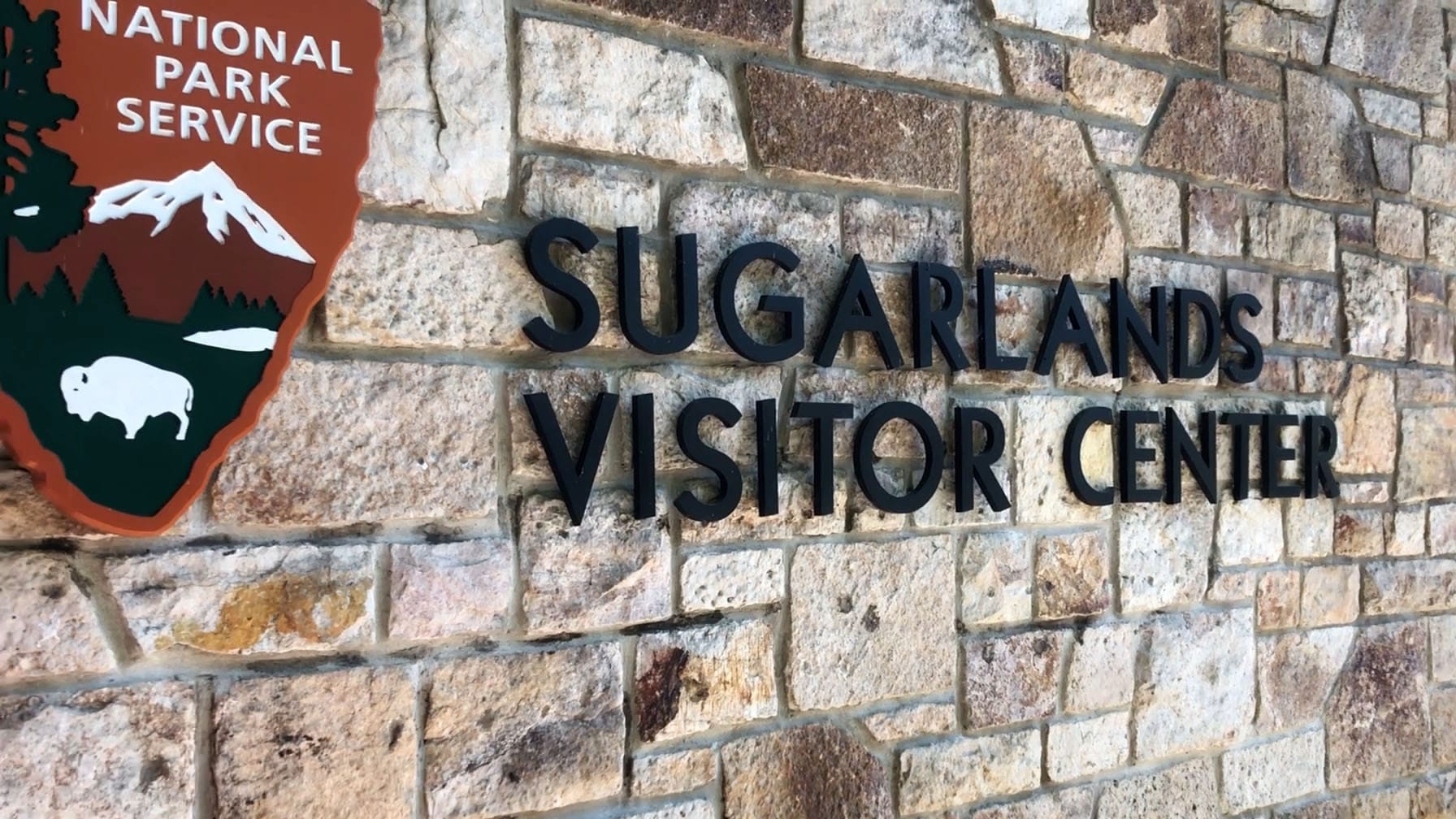 """Sugarlands Visitor Center"" sign against a brick wall."