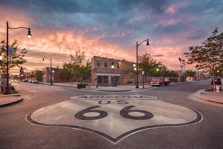 Route 66 painted on street corner in Winslow with pink and purple sunset