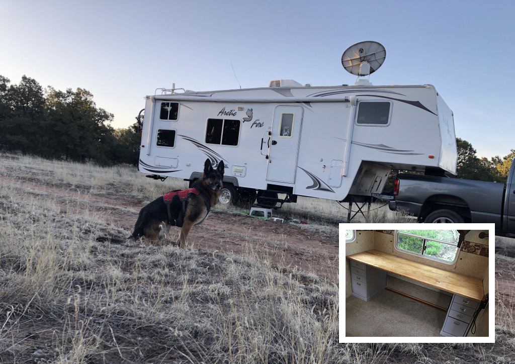 A German shepherd stands outside of a fifth-wheel with a satellite dish