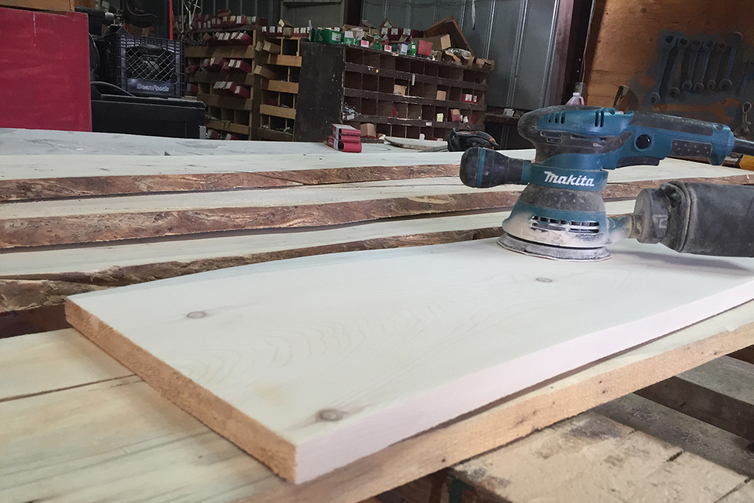 A Makita sander at rest atop a flat piece of wood in a workshop.