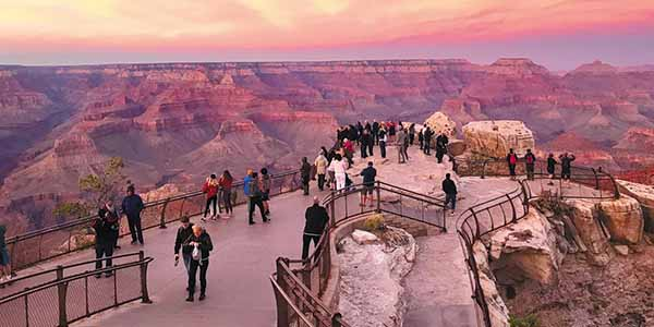 People standing on a fenced in area looking at the Grand Canyon
