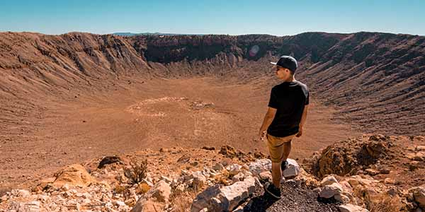 A man with a hat on standing at the top of the meteor crater