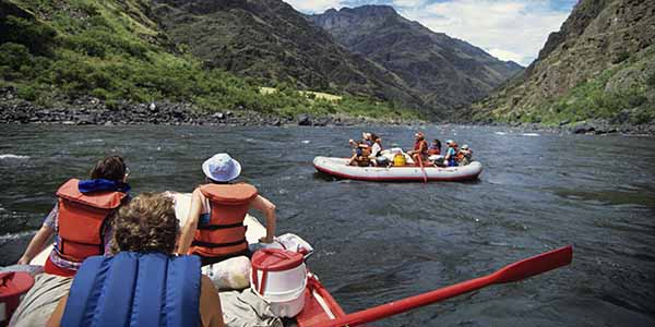 People with life vests in a raft on a river