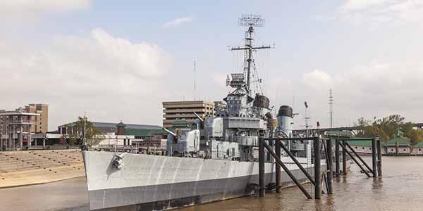 A historic World War II-era vessel on the muddy Mississippi River.