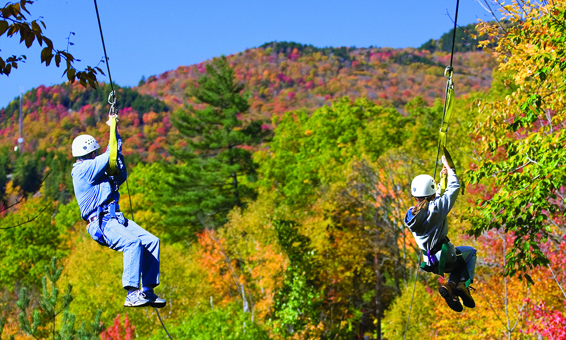 A senior man and a young woman zipline with fall foliage in the background.