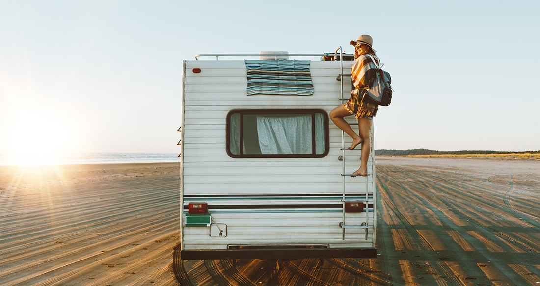 A woman in beach clothes scales the ladder of on the rear of a motorhome on an otherwise empty, sprawling beach.