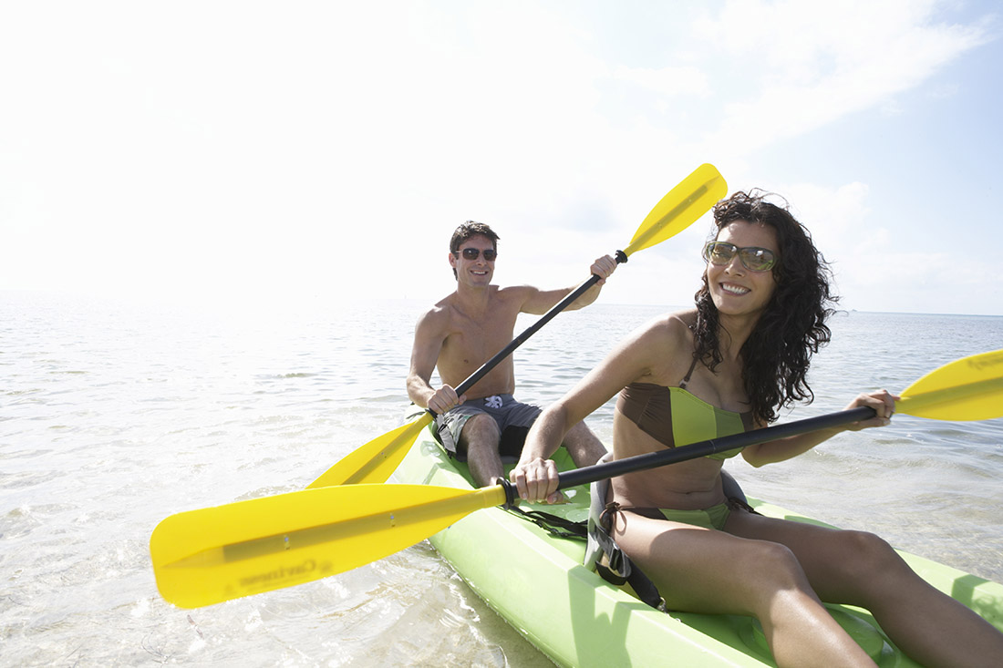 A smiling man and woman paddle a two-person green kayak with yellow paddles.