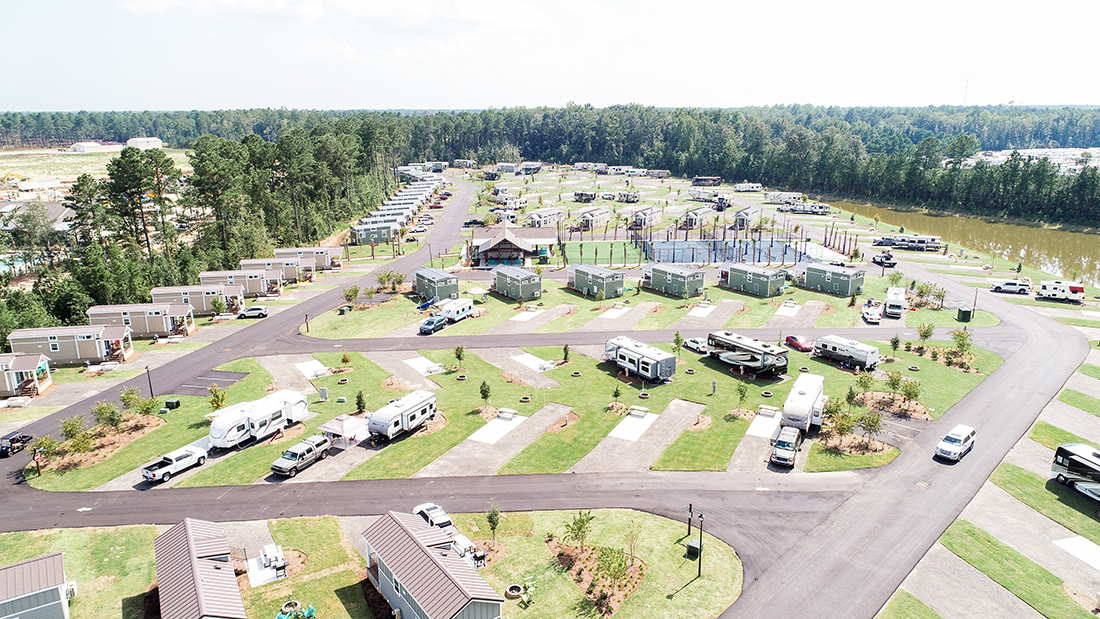 An aerial view of an RV park with neat concrete spaces and bordered with pine trees.
