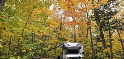 A Class C motorhome dry camping under golden leaves.