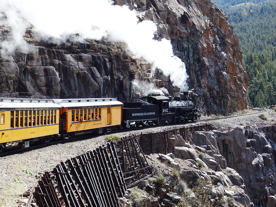 A black train engine pulls a pair of yellow cars along the face of a cliff.