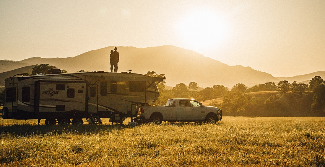 A couple stands on the roof of a fifth-wheel as the sun sets behind a mountain over a golden field.