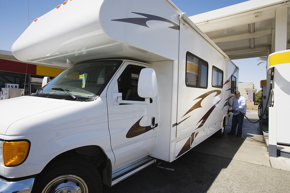 A man refuels a white minimotorhome adorned with teal and brown graphics.
